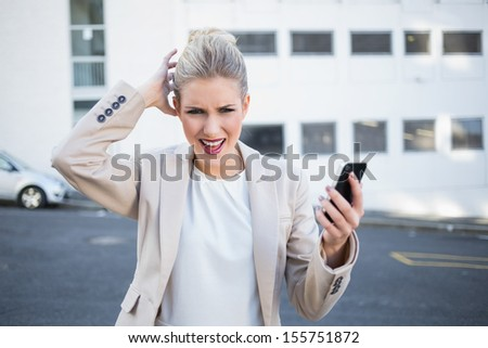 Furious stylish businesswoman holding her phone outdoors on urban background - stock photo