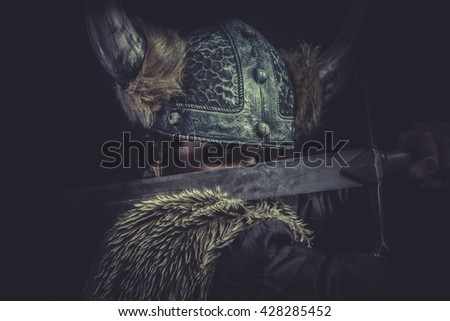 Furious, Viking warrior with a huge sword and helmet with horns - stock photo