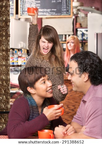 Furious woman throwing cup at cheating boyfriend in cafe - stock photo