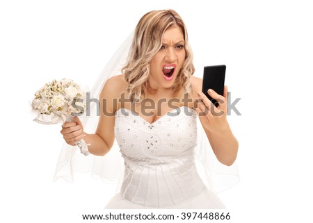 Furious young bride looking at her cell phone and screaming isolated on white background - stock photo