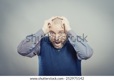 furious young men holding his head in hands and screaming - stock photo