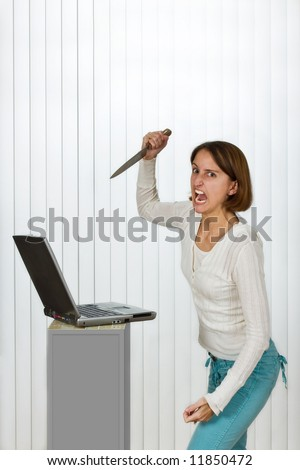 Furious young woman destroying a laptop computer with a knife. - stock photo