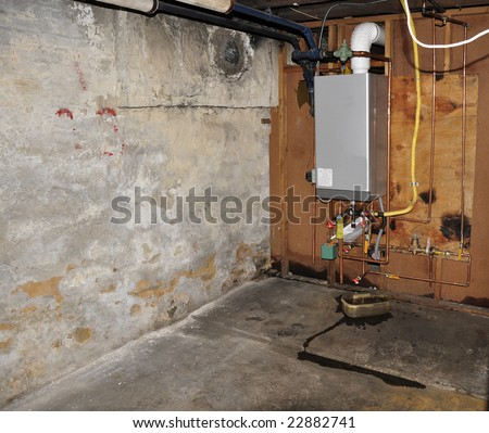 furnace heating unit on wall in an old basement - stock photo