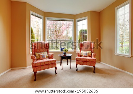 Furnished living room corner with antique pink chairs and dark brown table.