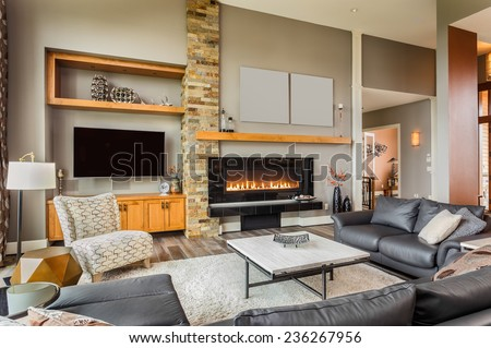 Furnished living Room in Luxury Home with Roaring Fireplace - stock photo