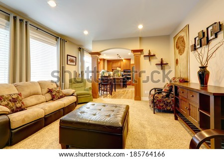 Furnished luxury living room with leather ottoman. View of fireplace with tv and built-in cabinet