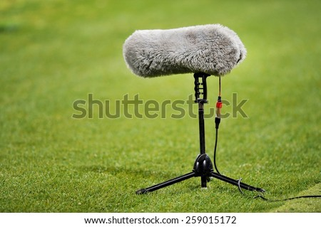 Furry sport microphone on a soccer field - stock photo