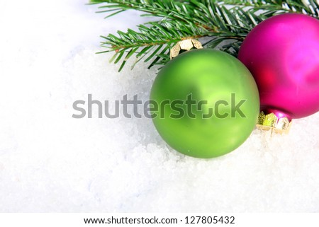 Fuschia and green Christmas baubles and pine tree branches on snow - stock photo