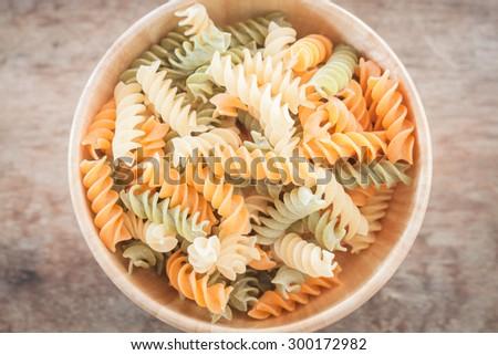 Fusili pasta in wooden plate, stock photo - stock photo