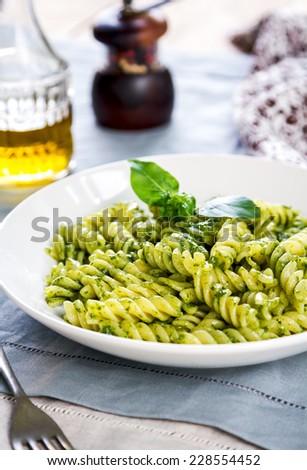 Fusilli in Pesto sauce by   olive oil and peper mill - stock photo