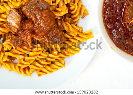 fusilli pasta al dente with neapolitan style ragu meat sauce very different from bolognese style - stock photo