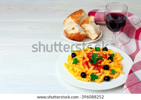 fusilli pasta and olives in the dish by fresh slices of bread on a saucer and glass of wine on a wooden white background with napkin