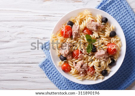 fusilli pasta with tuna, tomatoes and parmesan on the table. horizontal top view - stock photo