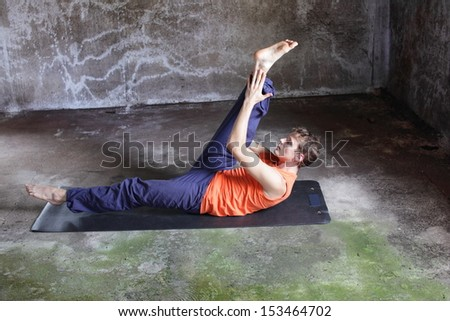 fusion of mind and body - caucasian man on mat practicing pilates - stock photo