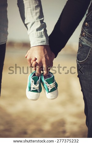 Future parents holding hands and a pair of little shoes - stock photo
