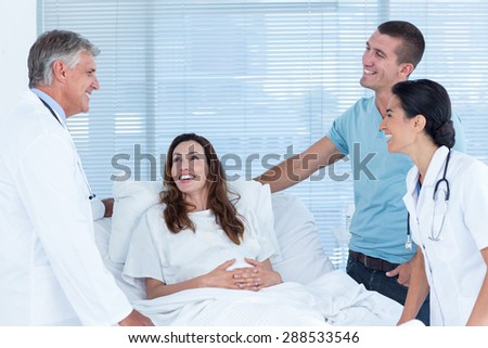 Future parents talking with smiling doctors in hospital room - stock photo