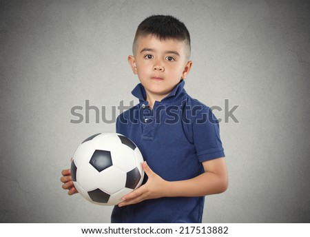 Future soccer player. Boy holding football ball isolated grey wall background. Confident face expression - stock photo