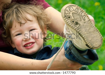 Future soccer player-mum dresses boots to the little boy after game in football on beach sand - stock photo