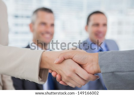 Future workmates shaking hands in bright office - stock photo