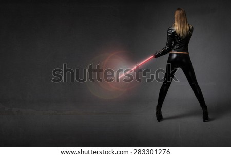 futurisitc soldier with weapon on hand, dark background - stock photo