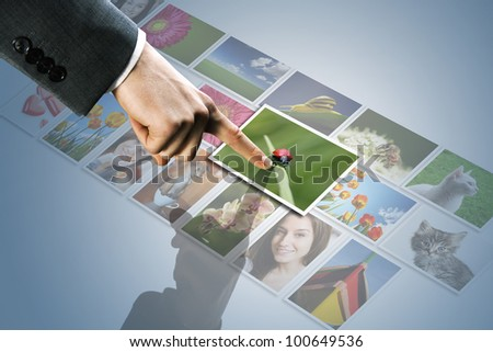 futuristic display:man hand reaching images on the screen