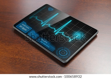 Futuristic medical tablet PC on table, showing cardiogram on display. - stock photo