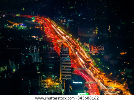Futuristic night cityscape aerial view panorama with illuminated skyscrapers and city traffic across streets. Bangkok, Thailand - stock photo
