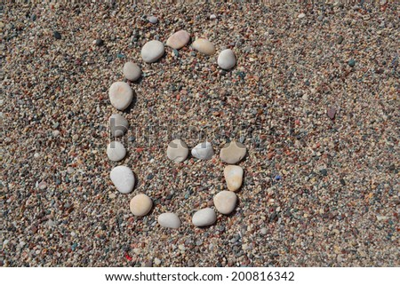 G letter made of stones on sand - stock photo