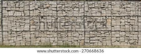 Gabion wall made of grey stones.  Stone wall. - stock photo