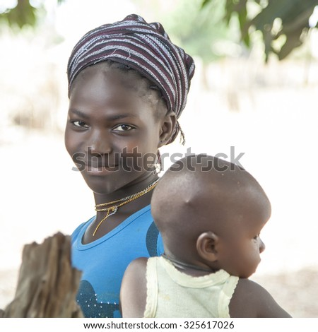 GABU, GUINEA-BISSAU - MAY 10, 2014: portrait of an unidentified beautiful african girl with her child