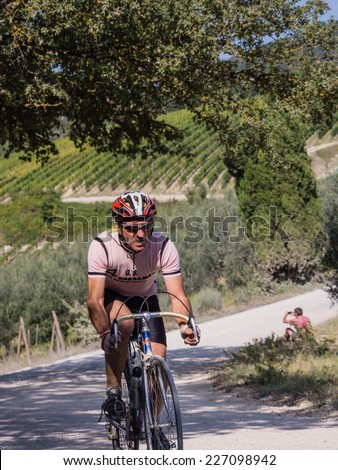 GAIOLE IN CHIANTI, ITALY - 5 OCT. 2014: Unidentified participant of L'Eroica, a historic cycling event for owners of vintage bicycles and apparel who ride through Tuscany on white gravel roads - stock photo