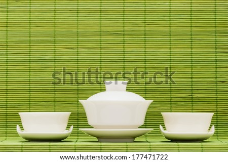 Gaiwan and drinking bowls for the Chinese tea against green bamboo sticks - stock photo