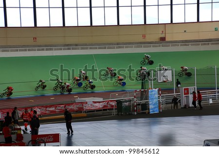 GALAPAGAR, SPAIN APRIL 6 - Cyclists in full competition for the final races of the championship of Spain for indoor track cycling teams - Cycle track of Galapagar,Spain April 2012 - stock photo