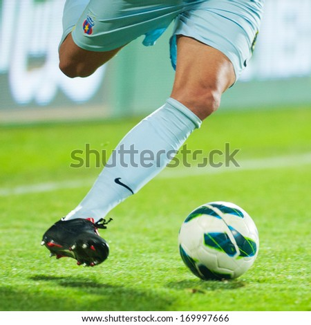 GALATI, ROMANIA - APRIL 2: Unknown football players performs during the soccer game in Liga 1, score 1-1, Otelul Galati (red and white) vs. Steaua Bucharest (blue) on April 2, 2013 in Galati, Romania - stock photo