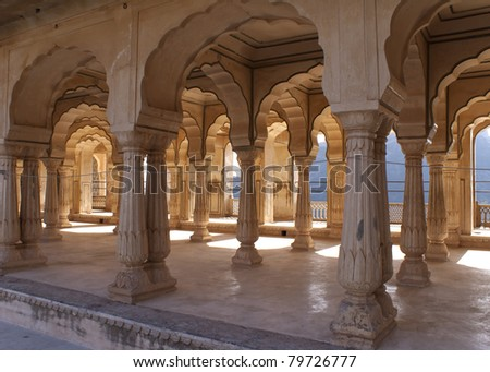 Gallery of rimmed pillars in light sunshine at Jaipur's Amber Fort.