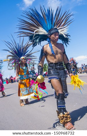 GALLUP , NEW MEXICO - AUGUST 10 :Aztec dancers with traditional costume participates at the 92 annual Inter-tribal ceremonial parade on August 10 , 2013 in Gallup New-Mexico