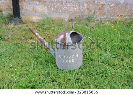 Galvanized Metal Watering Can, with Church Yard Painted on the Side, by the Church  in the Parish of St Margaret of Antioch, Tintinhull, Somerset, England, UK - stock photo