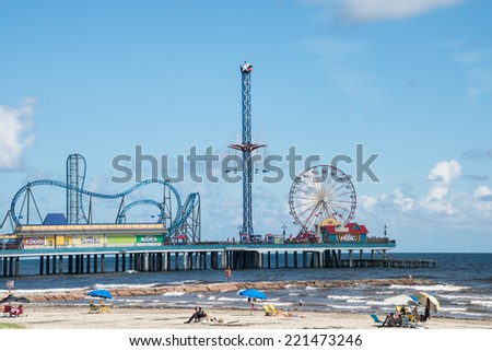 GALVESTON, TEXAS - SEPT 10, 2014: Historic Pleasure Pier amusement park and beach on the Gulf of Mexico coast in Galveston, Texas. - stock photo