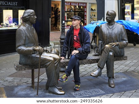 Galway, Ireland - August 26, 2014: Tourist on the bench with the Irish writer Oscar Wilde. Galway in Ireland