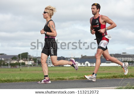 GALWAY, IRELAND - SEPTEMBER 2: Athletes T. Maxantova (269) and  S. Diez (140) competing at Course-Run, during 2nd Edition of Ironman 70.3 Galway 2012 Triathlon,on September 2, 2012 in Galway, Ireland. - stock photo