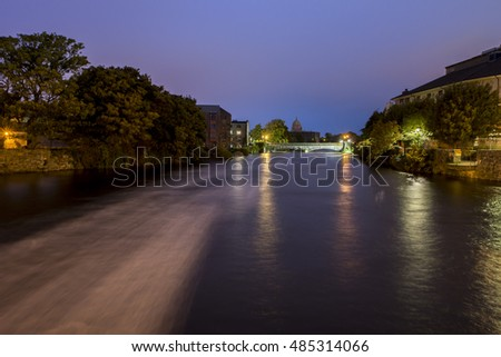 GALWAY, IRELAND - SEPTEMBER 18, 2016:Blurred waters of Corrib river and lights of Bridge Mill in the distance.