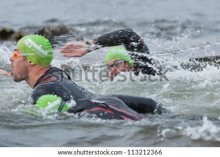 GALWAY, IRELAND - SEPTEMBER 2: Unidentified athletes  compete at the Course Swim during 2nd Edition of the annual Ironman 70.3 Galway 2012 Triathlon,on September 2, 2012 in Galway, Ireland. - stock photo