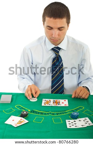 Gambler man in casino sitting at table with cards and poker chips isolated on white background