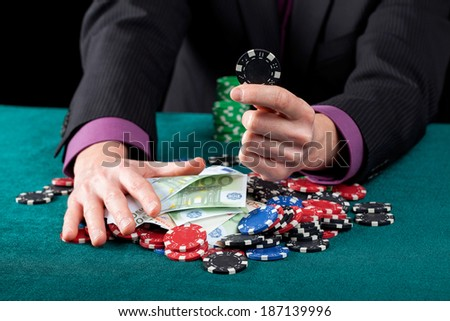 Gambler's hands with casino chips and banknotes