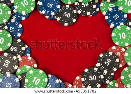 Gambling chips for poker around the red felt background - stock photo