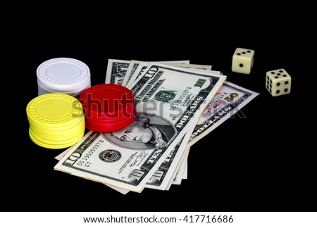 Gambling chips money and dice isolated against a black background - stock photo