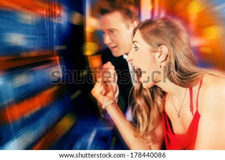 Gambling couple in Casino or amusement arcade on slot machine winning - stock photo