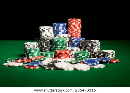 gambling, fortune, game and entertainment concept - close up of casino chips on green table surface - stock photo