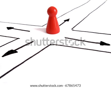Game figurine at crossroad, symbolizing the need to make a decision - stock photo