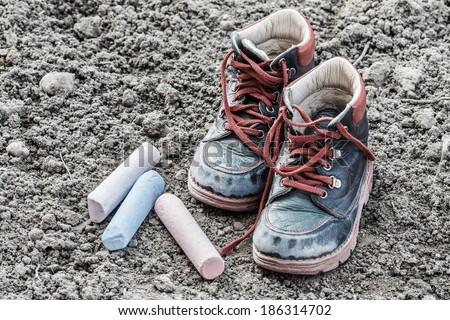 game over and back to school concept (old and dirty little baby booties on clay with chalks) - stock photo